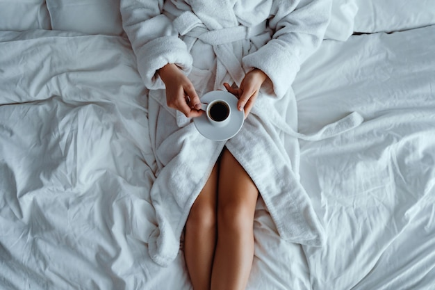 Ленивая женщина в халате, лежа на кровати и наслаждаясь ароматной чашкой кофе во время отдыха в уютной комфортной спальне в гостиничном номере.