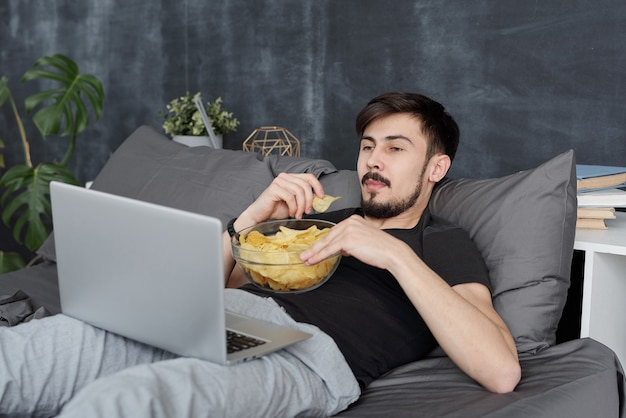 Ленивый молодой бородатый мужчина лежит на кровати и ест чипсы во время просмотра фильма на ноутбуке во время карантина из-за коронавируса