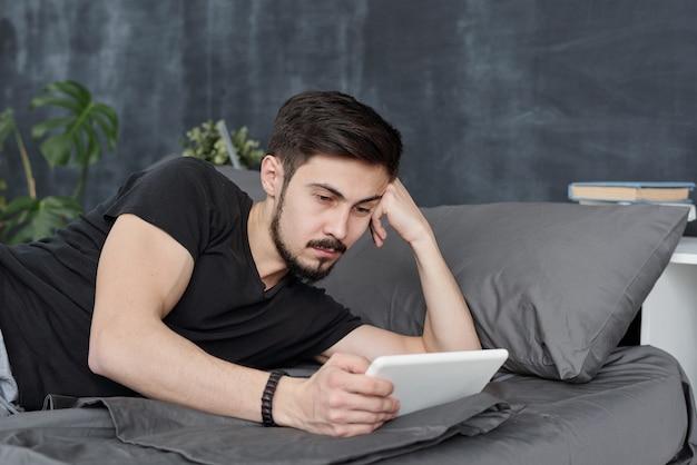 Ленивый молодой бородатый мужчина лежит на кровати и использует планшет, теряя время во время карантина