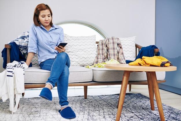 게으른 젊은 베트남 여성이 옷을 입고 소파에 앉아 소셜 미디어에서 게시물을 읽는 중