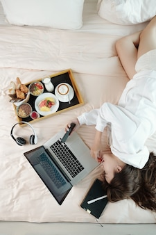 Lazy young woman lying on bed, eating breakfast and checking messages and e-mails on smartphone and laptop, view from above