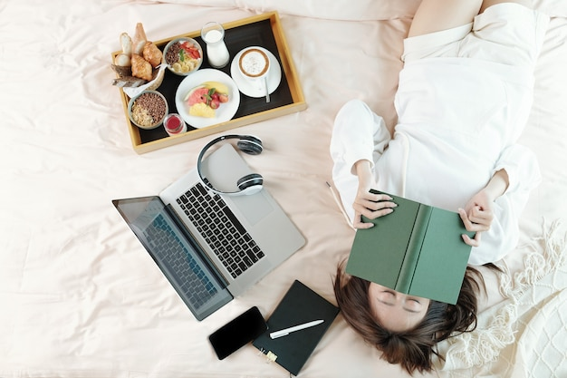 Lazy young woman lying on bed with opened laptop and tray with breakfast, sleeping after reading boring book