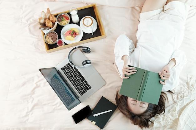 Ленивая молодая женщина, лежа на кровати с открытым ноутбуком и подносом с завтраком, спит после чтения скучной книги