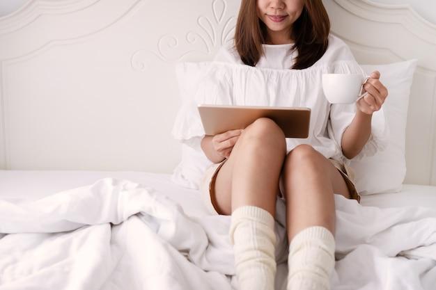 Молодая красивая брюнетка волосы женщина с помощью планшета и пить кофе, сидя на кровати в первой половине дня. крупным планом, концепция lazy выходного дня
