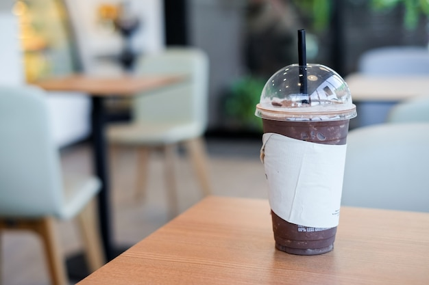 Lce cocoa or coffee in plastic glass with tissue on wooden table Premium Photo