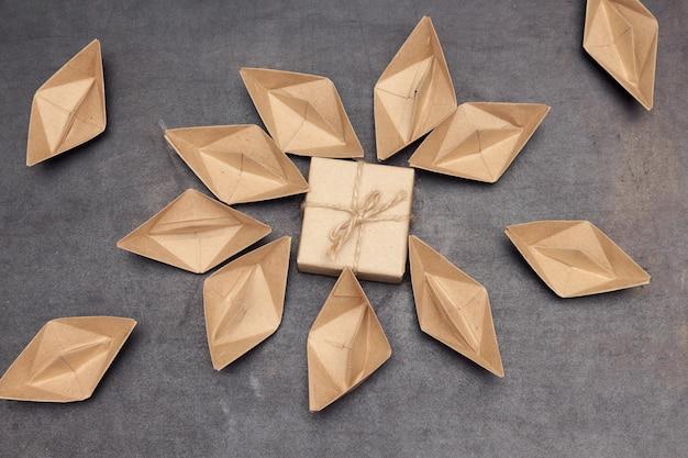Свинцовый магнит или подарки для подписчиков, привлекающих бумажные кораблики (люди). черный фон, плоская планировка, копия пространства.