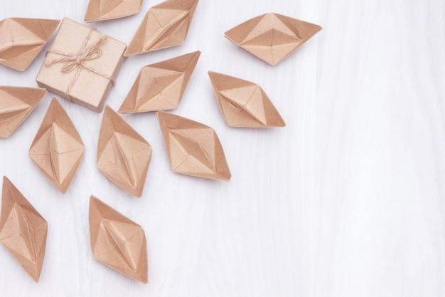 Свинцовый магнит или подарки для подписчиков, привлекающих бумажные кораблики (люди). белый фон, плоская планировка, копия пространства.