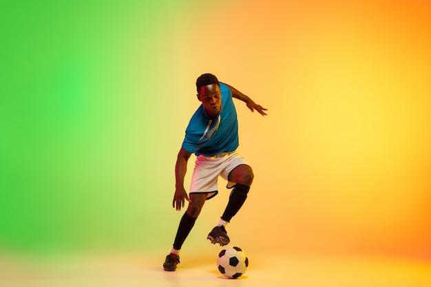 リーダー。アフリカ系アメリカ人の男性サッカー、ネオンの光の中でグラデーションスタジオの背景に分離されたアクションでトレーニングをしているサッカー選手。動き、行動、成果、健康的なライフスタイルの概念。若者文化。