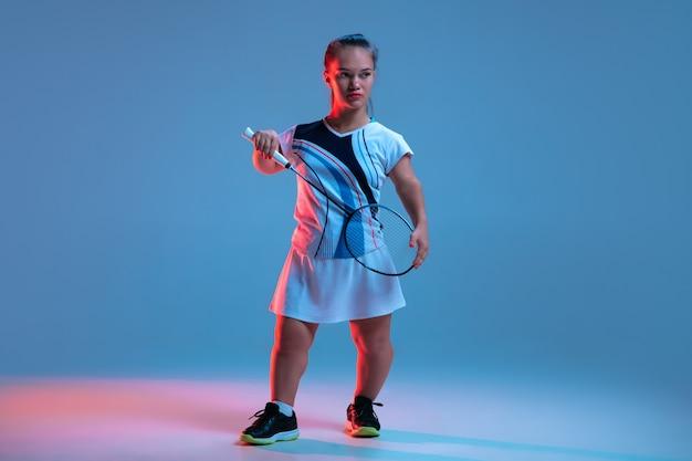 リーダー。ネオンの光の中で青に分離されたバドミントンで練習している美しい小さな女性。包摂的な人々のライフスタイル、多様性と平等