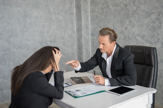 Leader businessman blaming female employee at office desk. fail business concept.