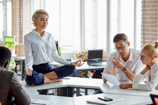 Leader of company sits in yoga pose, business woman in formal wear sits with crossed legs in lotus pose