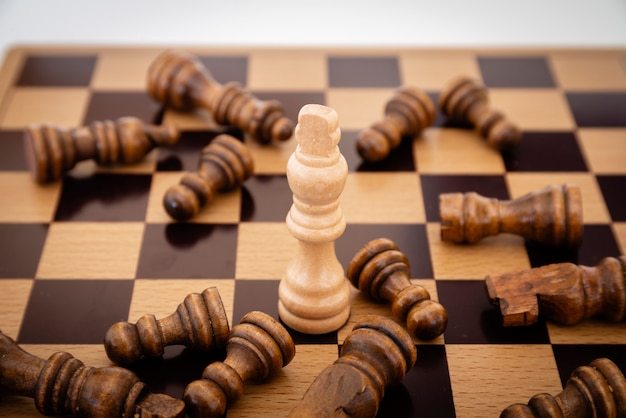 Leader and competition. white chess king among lying down black pawns on chessboard