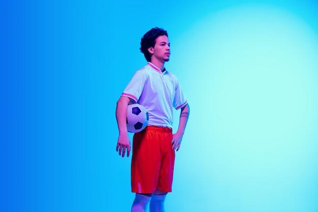 지도자. 네온 불빛의 그라데이션 파란색 스튜디오 벽에 있는 축구 또는 축구 선수 - 공을 가지고 자신감 있게 포즈를 취합니다. 카피스페이스.