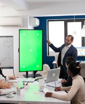 多様なチームのブレーンストーミングの前でモックアップディスプレイを使用して財務計画を提示する会社のリーダー。マネージャーは、会議室のクロマキーデスクトップを備えたグリーンスクリーンモニターでプロジェクト戦略を説明します
