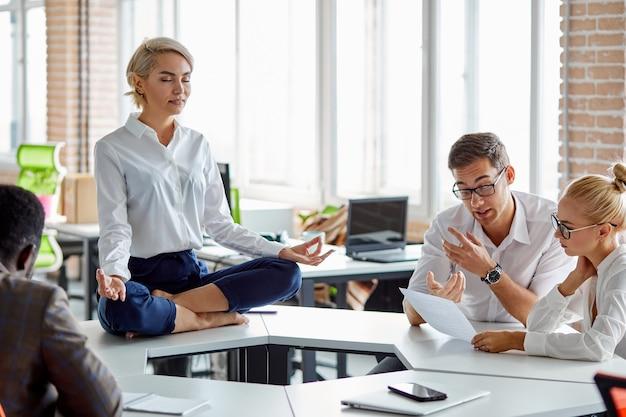 회사의 지도자는 요가 포즈에 앉아 있고, 공식적인 마모에 비즈니스 여성은 연꽃 포즈에서 다리를 건너 앉아 앉아