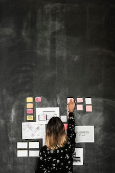 Leader in a startup company brainstorming using a blackboard