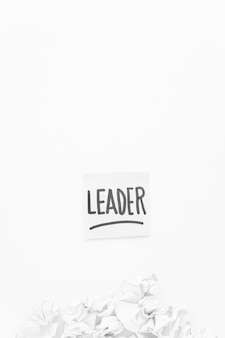 Leader text on adhesive note with crumpled paper on white background