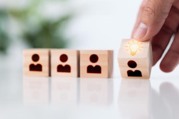 アイデアと革新のリーダーである男の手は、アイコンの電球と人間のシンボルで立方体を反転します。