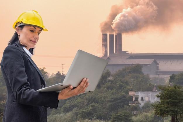 공장 배경 굴뚝에서 타는 연기를 확인하는 노트북을 들고 있는 리더 여성 엔지니어