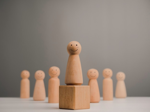 Leader woman, influencer, women in leadership position concept. wooden figure, happy and strong female with smiling standing on the box and team, minimal style.