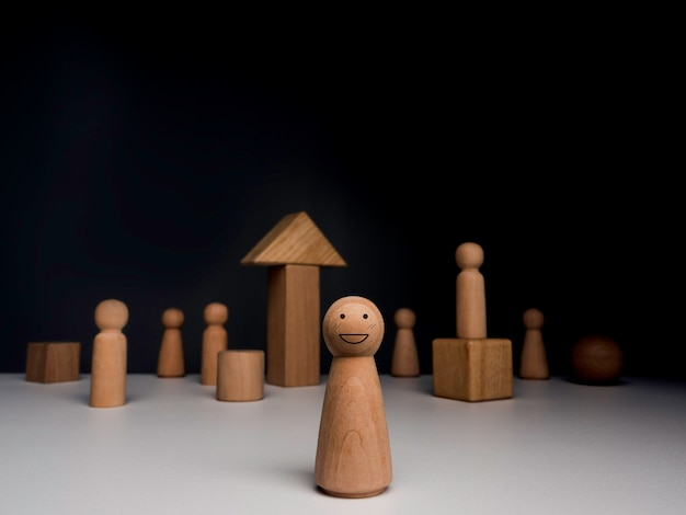Leader woman, influencer, women in leadership position concept. the wooden figure, strong female standing in front of the community, wood blocks on dark background, minimal style.