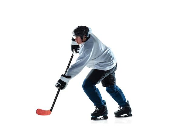 Capo. giovane giocatore di hockey maschio con il bastone sul campo di ghiaccio e sfondo bianco. sportivo che indossa attrezzatura e casco che pratica. concetto di sport, stile di vita sano, movimento, movimento, azione.