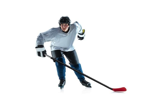 리더. 아이스 코트와 흰색 배경에 막대기로 젊은 남자 하키 선수. 장비와 헬멧 연습을 착용하는 스포츠맨. 스포츠, 건강한 라이프 스타일, 운동, 운동, 행동의 개념.