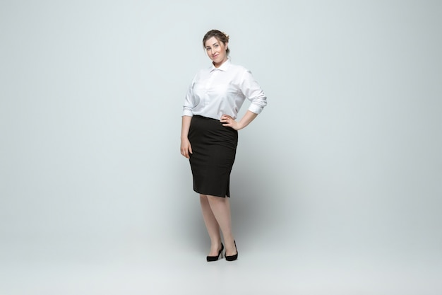 Leader. young woman in office attire. body positive female character, feminism, loving herself, beauty concept. plus size businesswoman on gray wall. boss, beautiful. inclusion, diversity.