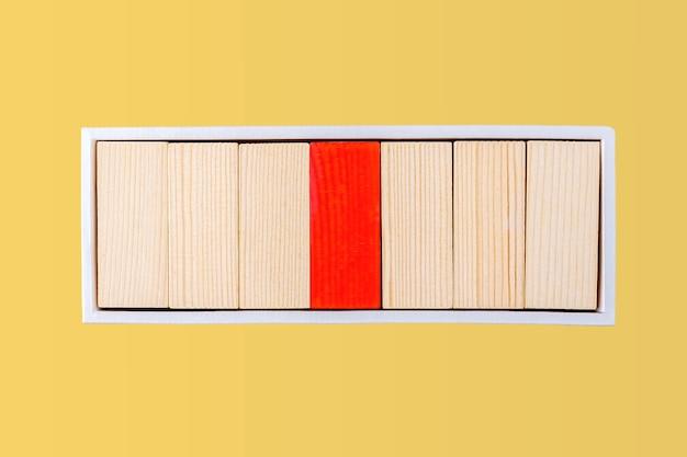 Концепция лидерства и влияния. один красный и много деревянных блоков штабелируются в коробке. индивидуальность и неповторимость. доминирующий лидер или босс