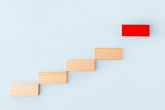 리더십과 영향력 있는 사람 개념. 나무 블록은 계단으로 쌓이고 파란색 배경에 빨간색 하나를 따라갑니다. 개성과 독창성. 사회적 거리. 지배적인 지도자.