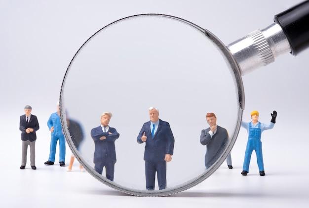 リーダーシップと管理の概念。スタッフと拡大鏡ガラスで立っているビジネスマンのミニチュア。