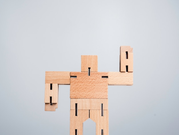 Leadership concept. the leader or influencer, wooden robot strong power gesture standing isolated on white background, minimal style.