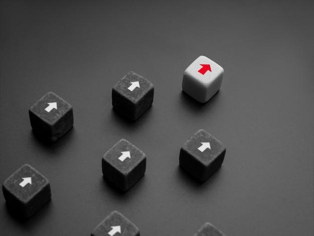 リーダーシップの概念、マネージャー、ceo、インフルエンサー、オピニオンリーダー、ビジネスリーダー。白いサイコロに赤い矢印の付いたリーダーが白い矢印の付いた黒いサイコログループをリードし、暗い背景にフォロワーがいます。