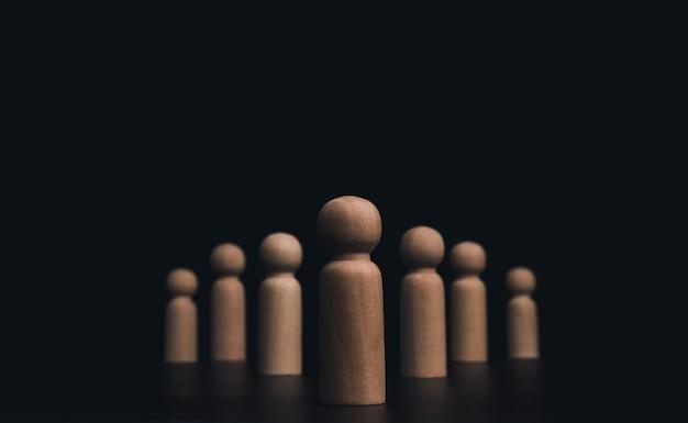 リーダーシップの概念、マネージャー、ceo、マーケットリーダー、インフルエンサー、オピニオンリーダー、ビジネスリーダー。コピースペースのある暗い背景に、フォロワーのいるリーダーの木像が整然と並んでいます。