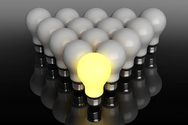 Концепция лидерства. одна светящаяся лампочка стоит перед не зажженной на черном фоне