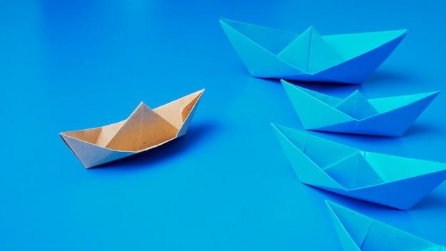 Leadership concept origami boat paper