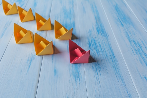 Leadership concept, red leader boat, standing out from the crowd of orange boats