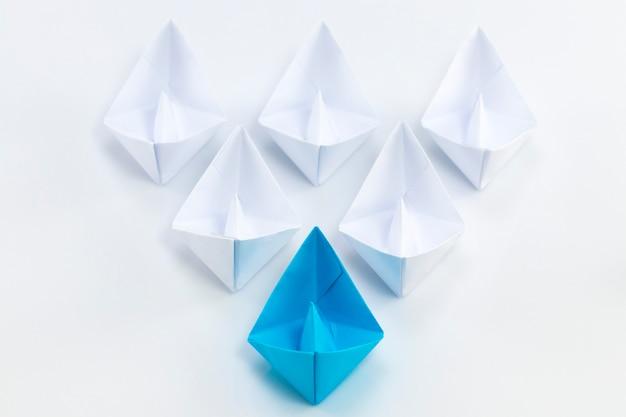 Концепция лидерства с использованием синего бумажного корабля среди белых.