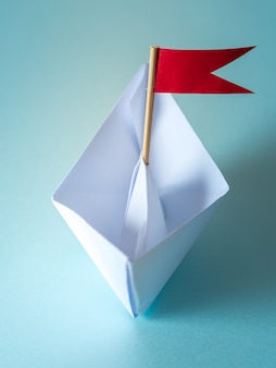 Leadership concept using  paper ship with red flag on blue background