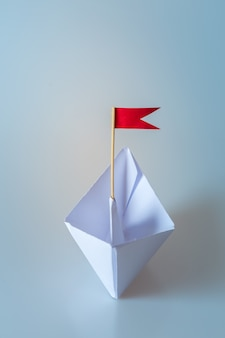 Leadership concept using  paper ship with red flag on blue