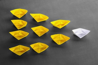 Leadership concept white leader paper boat standing out from the crowd of yellow boats