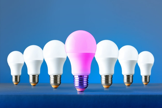 Leadership concept with neon light bulb leading among white on blue background