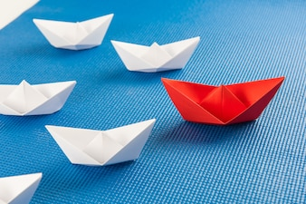Leadership concept with red paper ship leading among white and blue background