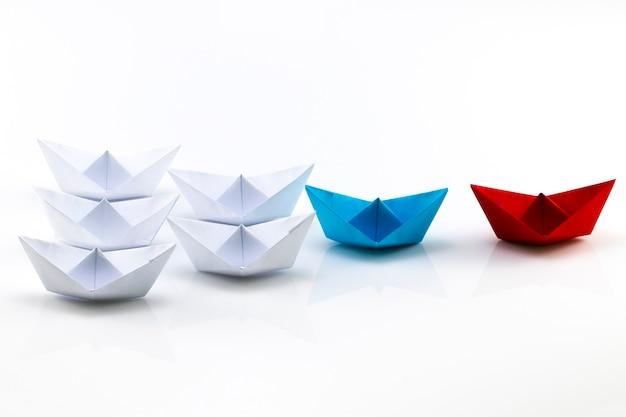 Концепция лидерства с красным бумажным кораблем, ведущим среди белых.