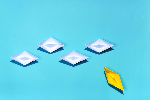 Концепция лидерства. желтый бумажный корабль, ведущий среди белых