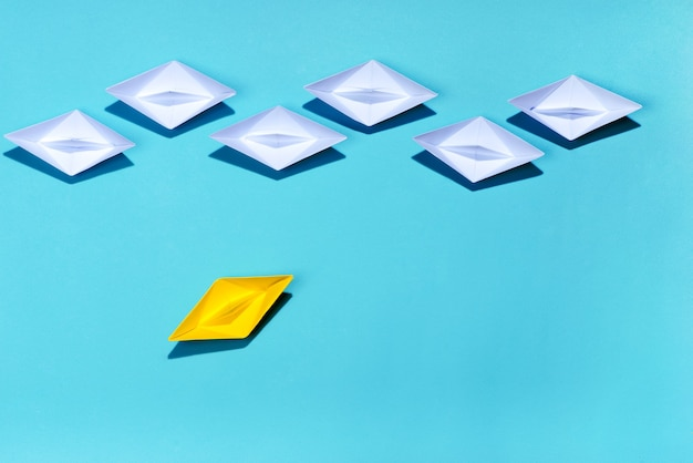 Leadership concept. yellow paper ship leading among white