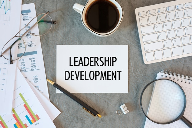 Leadership development is written in a document on the office desk with office accessories, coffee, diagram and keyboard