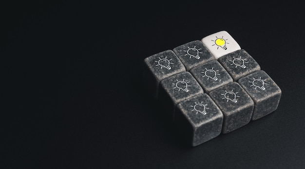 Leadership, smart learning, knowledge and creative idea concept. glow difference light bulb icon symbol on white dice blocks with black pieces on dark background with copy space, minimal style.