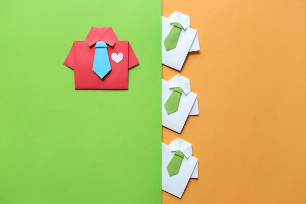 Leadership and teamwork concept, origami red shirt with tie and leading among small yellow shirt