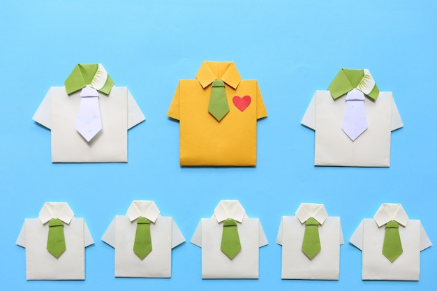 Leadership and teamwork concept, origami yellow shirt with tie and leading among small yellow shirt
